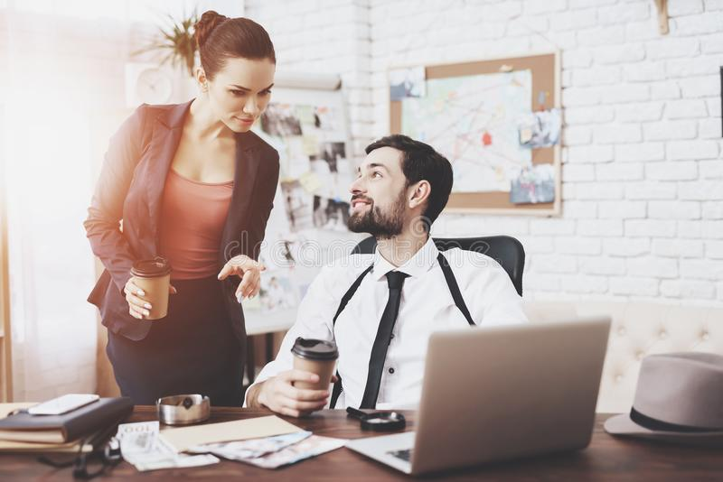 Private detective agency. Man and woman are talking, drinking coffee. Private detective agency. Man with holsters and women are talking, drinking coffee royalty free stock photo