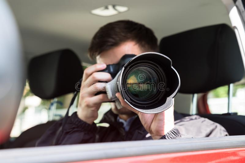 Private Detective Photographing With Slr Camera. Side View Of A Private Detective Sitting Inside Car Photographing With Slr Camera royalty free stock image
