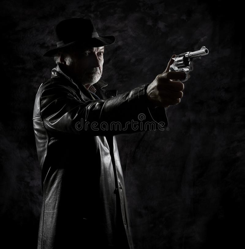 A private detective with a revolver in front of a black backdrop stock image