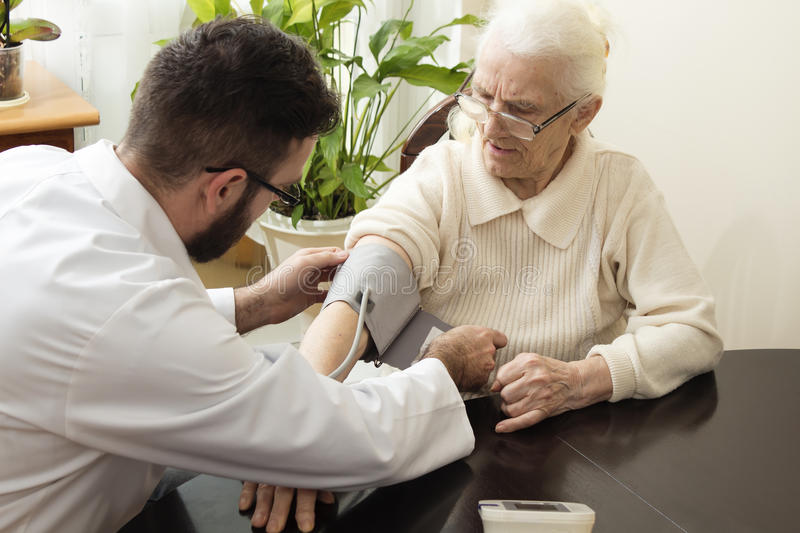 A private doctor`s office. Geriatrician doctor takes the patient and measure her blood pressure. royalty free stock photo