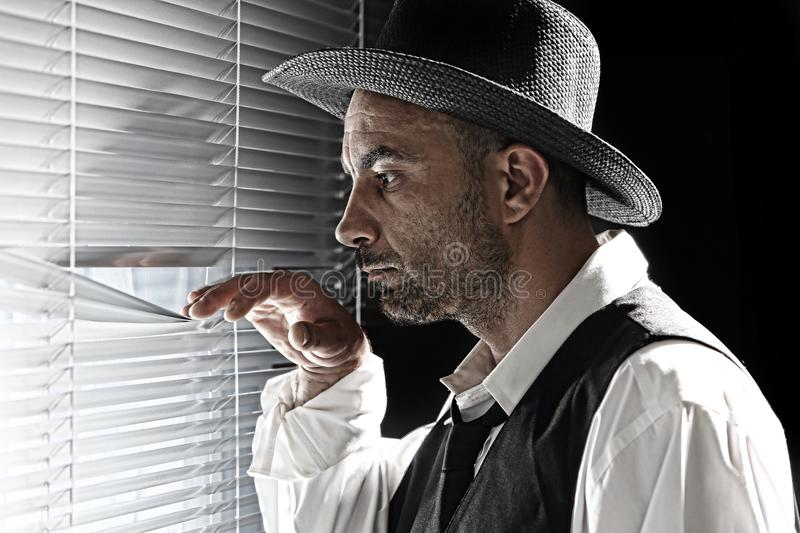 A private eye. Private detective watching through the blinds stock image