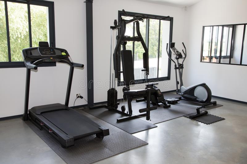 Private gym at home interior with different sport exercise equipment stock images