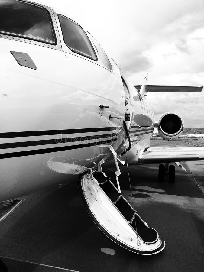 Private Jet parked at an Airport in Black & White. Private jet sitting on the tarmac with its door open urging you to come aboard. Also captures the jet engine royalty free stock image