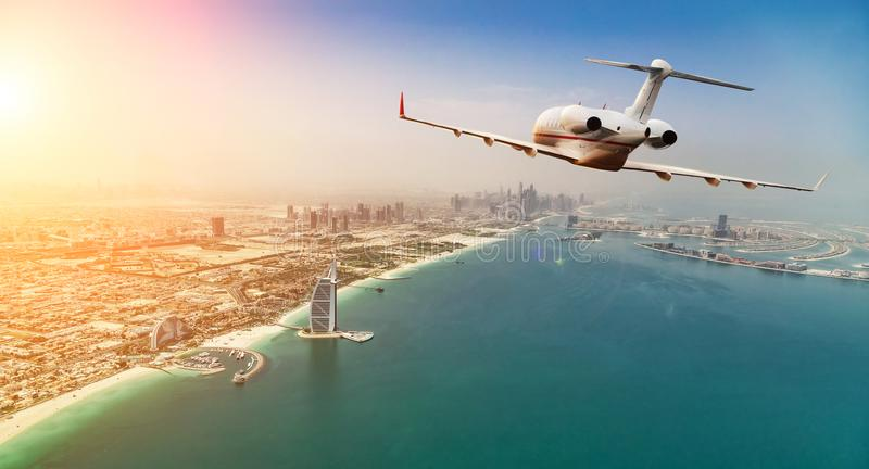 Private jet plane flying above Dubai city in beautiful sunset li royalty free stock photography