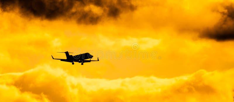 Private Jet Silhouette. A private jet silhouetted against the cloudy and overcast sky stock photos