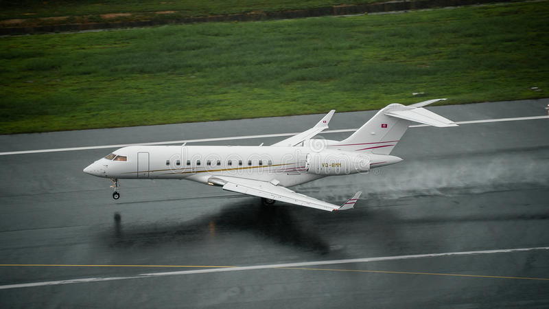 Private jet type Bombardier global 5000 landing on wet runway at royalty free stock photo