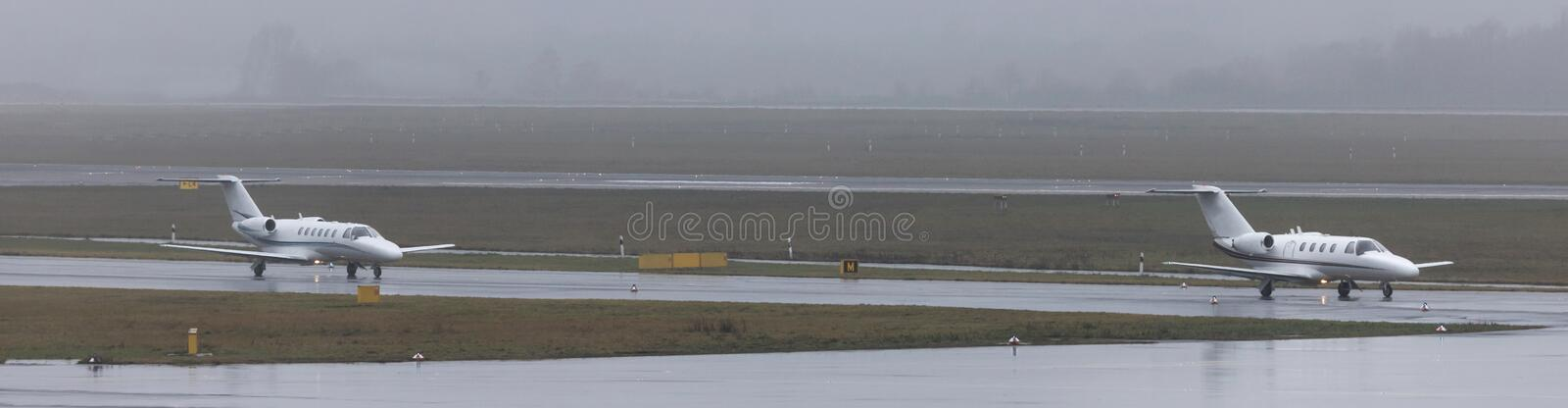 Private jets on an rainy airport panorama royalty free stock images