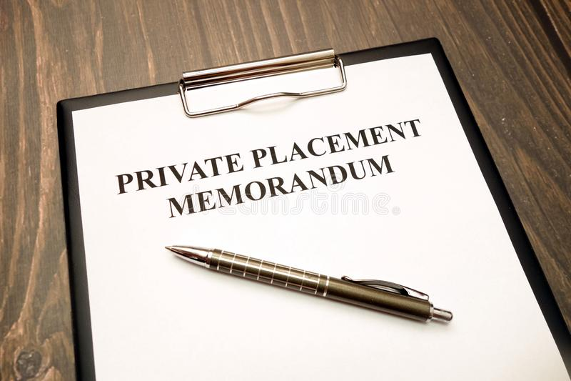 Private placement memorandum document with pen on desk. Private placement memorandum document with pen on wooden desk in office stock photo