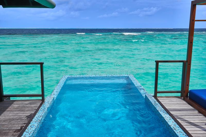 A private pool in a water villa in Coco Bodu Hithi resort, Maldives with scenic view of turquoise Maldives sea and clouds stock images