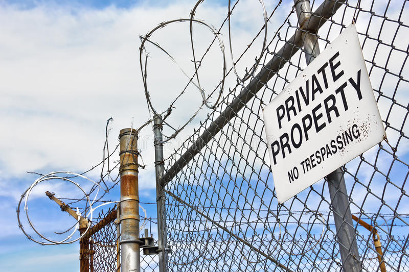 Private Property Sign on Fence. Barb wire used on top of a metal fence, with a private property sign hanging on the side royalty free stock photo