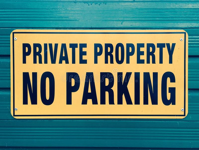 Private property sign. Yellow sign attached to a coloured wall telling passersby not to park here as this is private property royalty free stock photo
