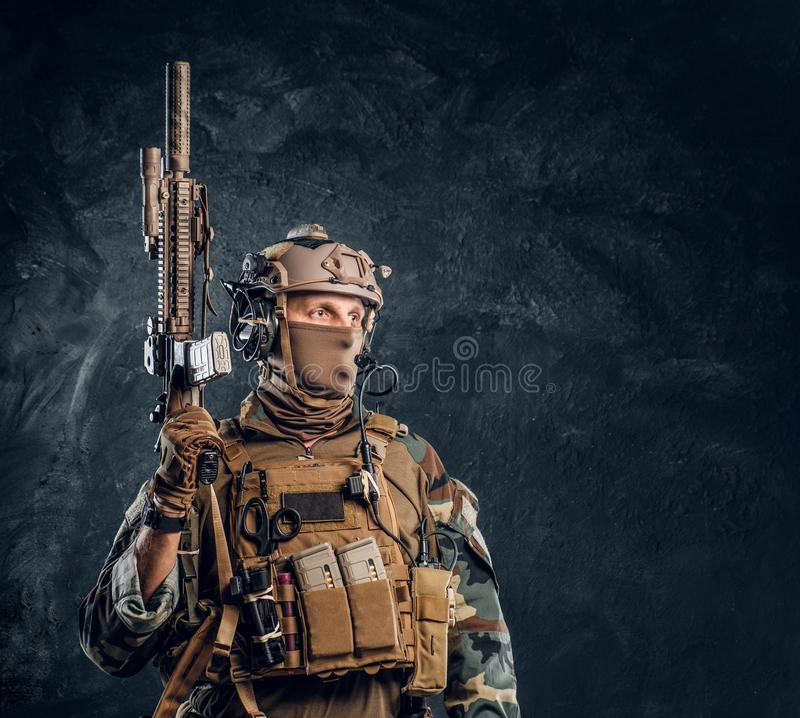 Elite unit, special forces soldier in camouflage uniform posing with assault rifle. Private security service contractor in camouflage uniform posing with royalty free stock photography