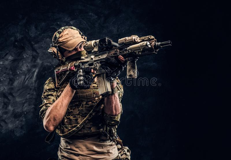 The elite unit, special forces soldier in camouflage uniform holding an assault rifle with a laser sight and aims at the royalty free stock photo