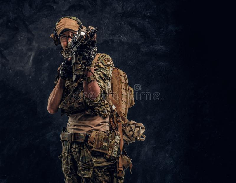 The elite unit, special forces soldier in camouflage uniform holding an assault rifle with a laser sight and aims at the. Private security service contractors stock image