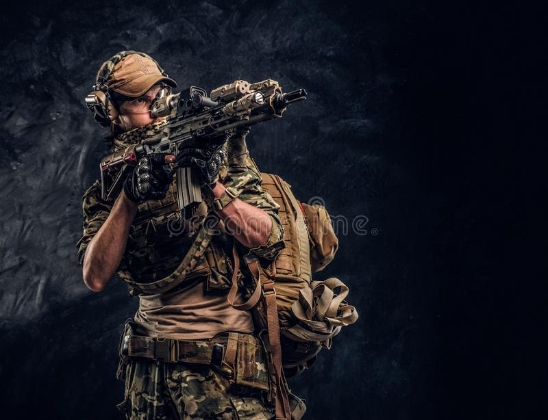 The elite unit, special forces soldier in camouflage uniform holding an assault rifle with a laser sight and aims at the. Private security service contractors royalty free stock photography