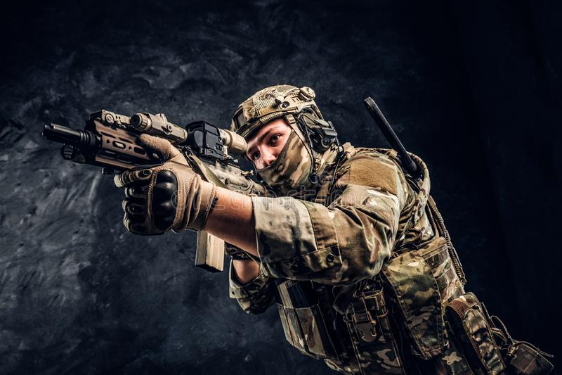 The elite unit, special forces soldier in camouflage uniform holding an assault rifle with a laser sight and aims at the stock images