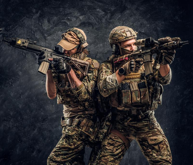 Private security service contractors, the elite special unit, full protective soldiers aiming at the targets. royalty free stock photo