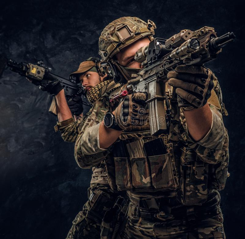 Private security service contractors, the elite special unit, full protective soldiers aiming at the targets. royalty free stock photos