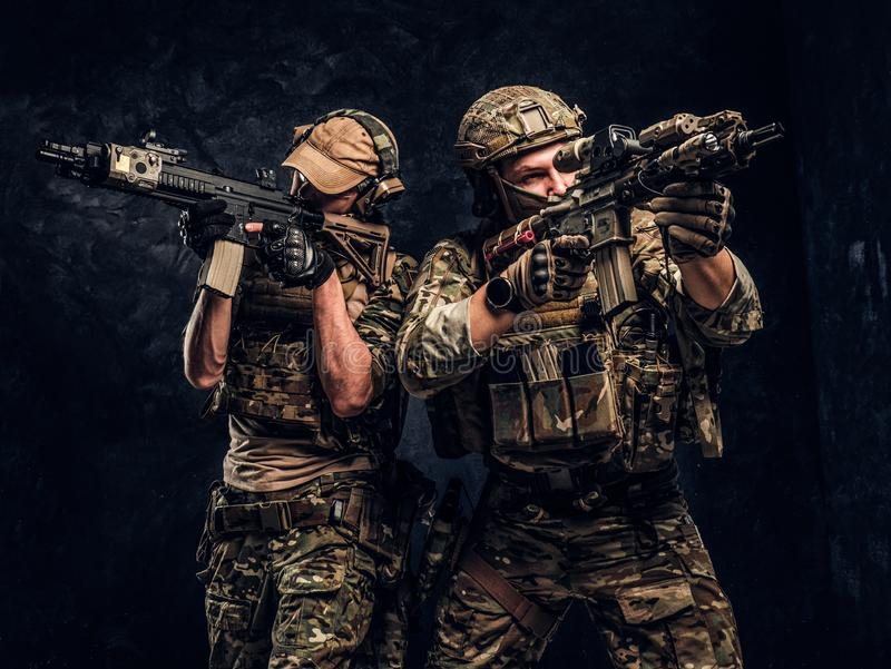 Private security service contractors, the elite special unit, full protective soldiers aiming at the targets. royalty free stock photography