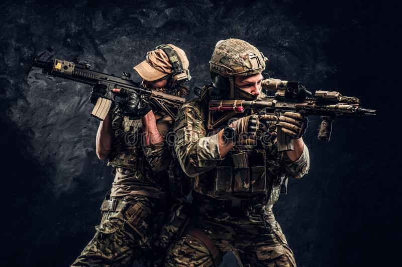 Private security service contractors, the elite special unit, full protective soldiers aiming at the targets. stock image