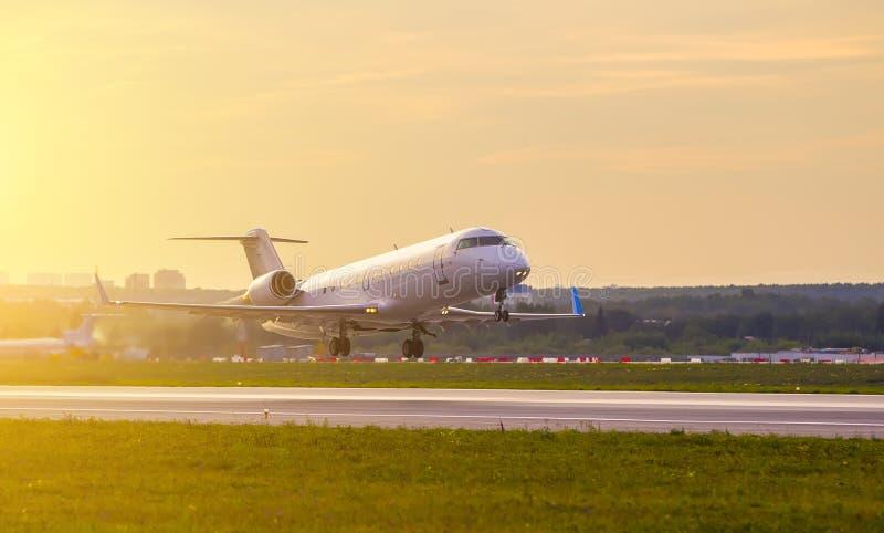 PrivatsacheDüsenflugzeug startet vor dem hintergrund der Sonnenuntergangwolken und des goldenen Lichtes von der Sonne stockbilder