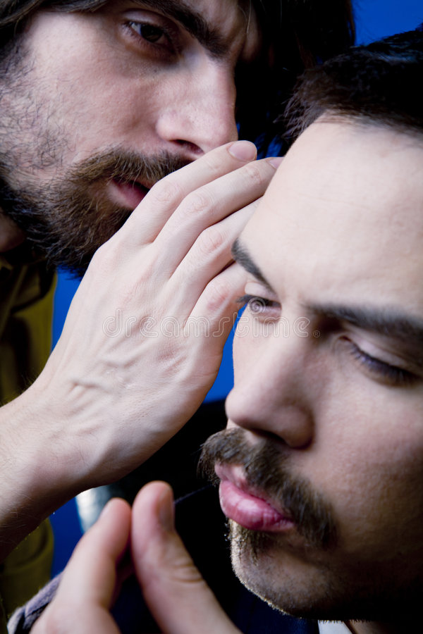Privileged Information. Closeup of a man whispering confidentially into the ear of another man, both with serious expressions royalty free stock image