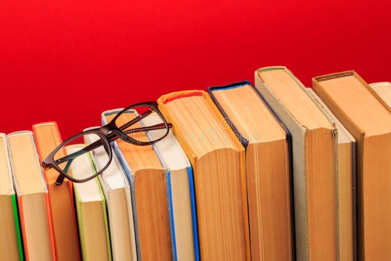Prości skład hardback książki, surowy książki na drewnianym pokładu stole z szkłami i czerwonym tłem zdjęcia stock