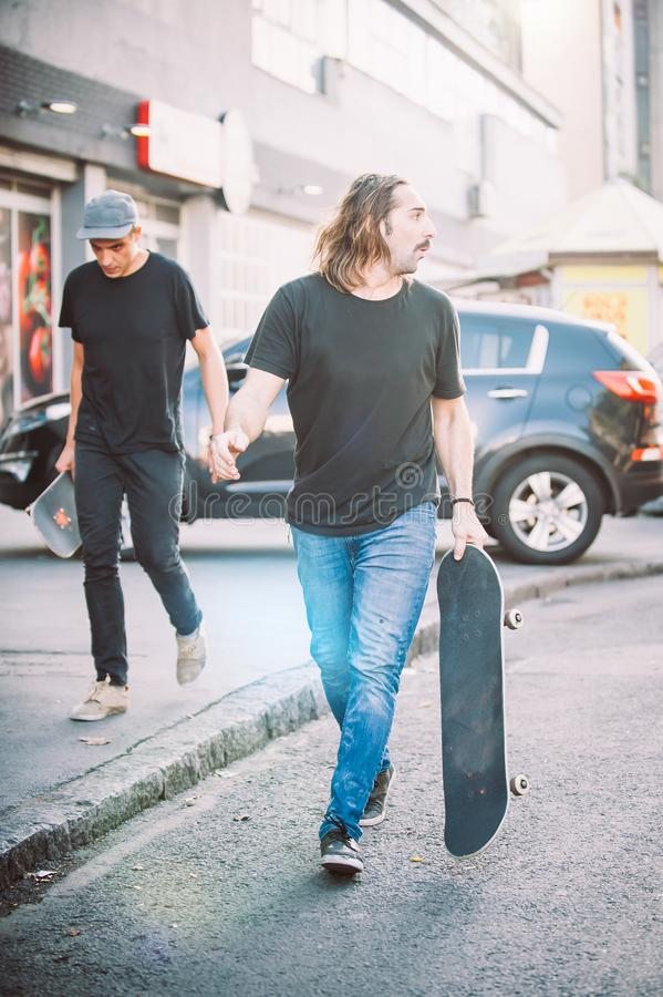 Pro всадник скейтборда 2 идя вниз с улицы держа skatebo стоковая фотография