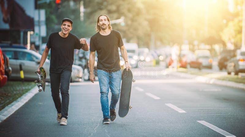 Pro всадник скейтборда 2 идя вниз с улицы держа skatebo стоковое изображение