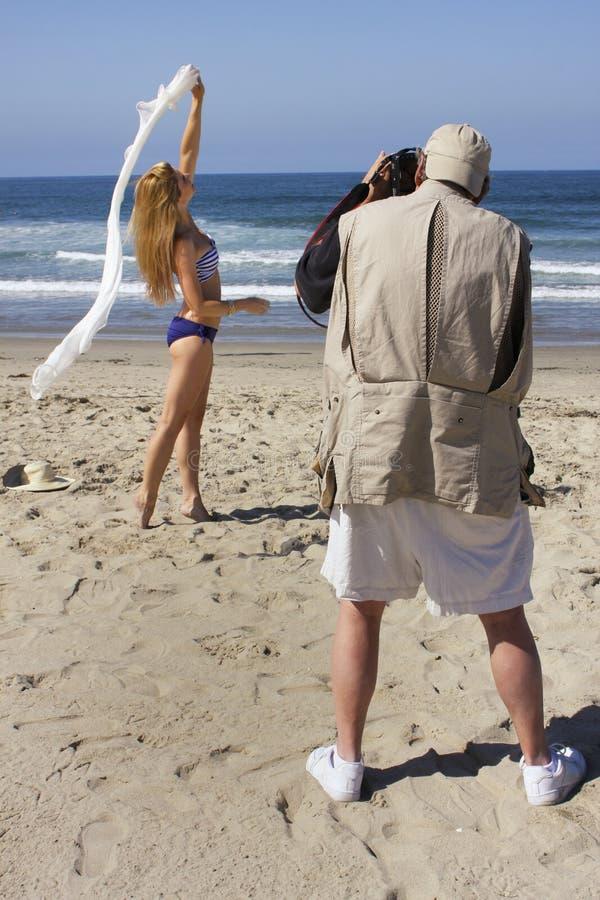Pro фотограф работая с моделями на пляже стоковое изображение