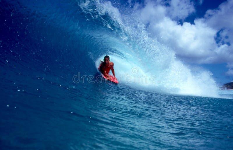 Pro Bodyboarder Alex Kinimaka in un'onda blu del tubo immagine stock
