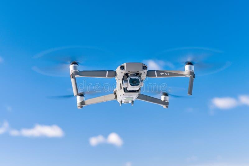 Pro bourdon de DJI Mavic 2 pendant le vol contre le ciel bleu image libre de droits