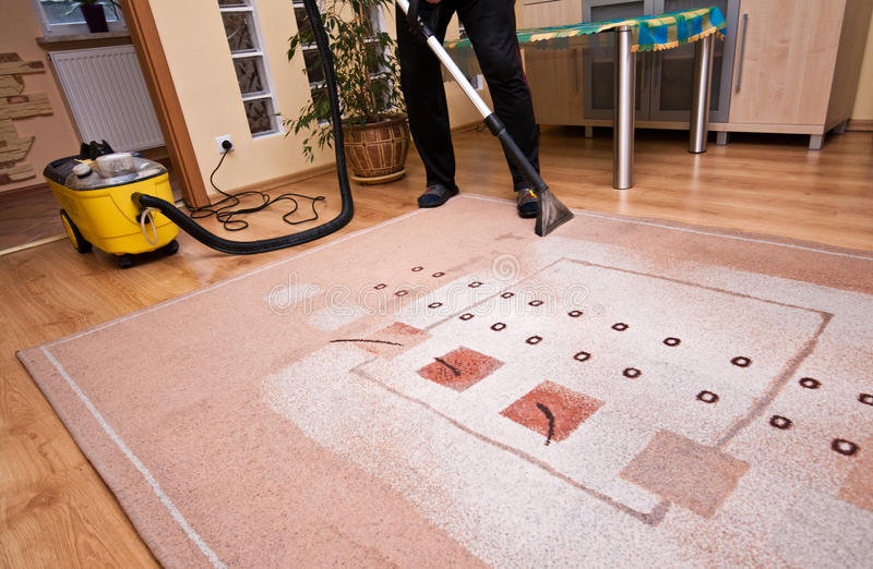Pro cleaning services. Vacuum cleaning a carpet stock photo