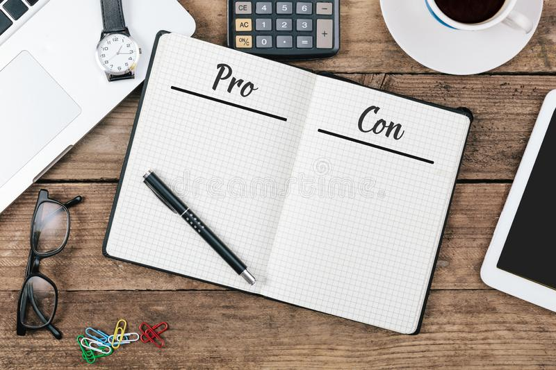 Pro and Con lists in note pad on office flat lay. Pro and Con pages written in note pad on wooden office technology desk flat lay royalty free stock photo