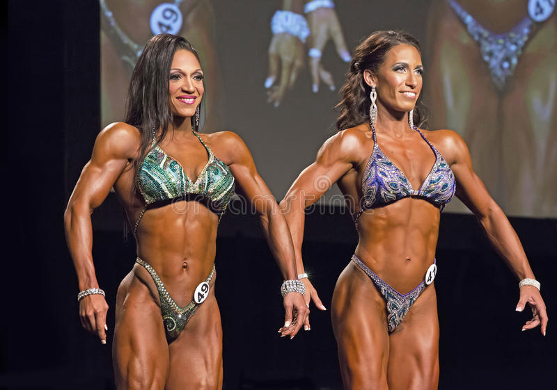 Pro Figure Winner from Trinidad. Candice John of Trinidad (left) poses with Jennifer Brown from the USA (4th place) in the Pro Figure contest of the 2015 IFBB royalty free stock photos