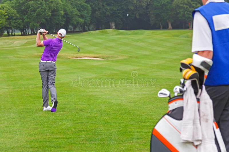 Pro golfer playing a shot with caddy stock photo