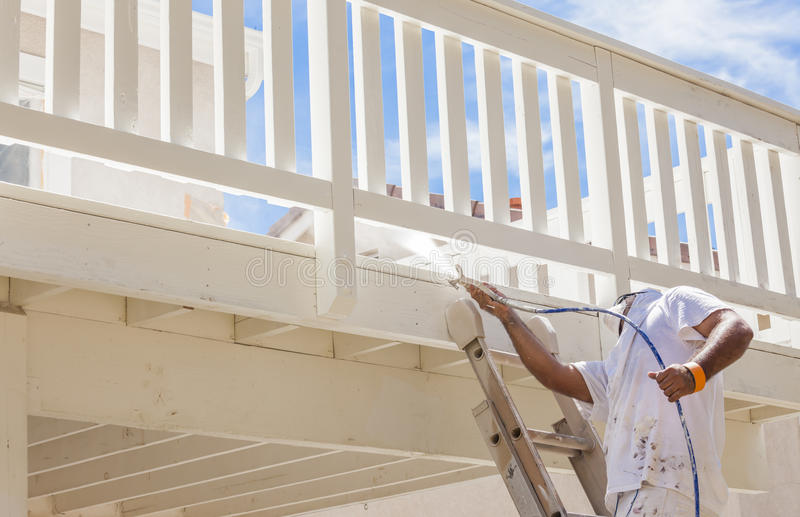 Pro House Painter Spray Painting A Deck of A Home. House Painter Wearing Facial Protection Spray Painting A Deck of A Home royalty free stock image