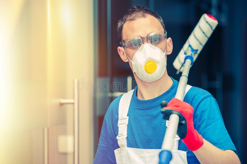 Pro House Painting. Professional House Painter with Painting Roller, Safety Mask and Glasses. Indoor Painting royalty free stock image