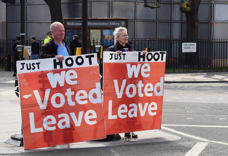 Brexit pro leave protesters in Parliament Square Westminster London. March 28 2019. A pro leave the EU protester couple with signs that read `We Voted Leave` in stock photos