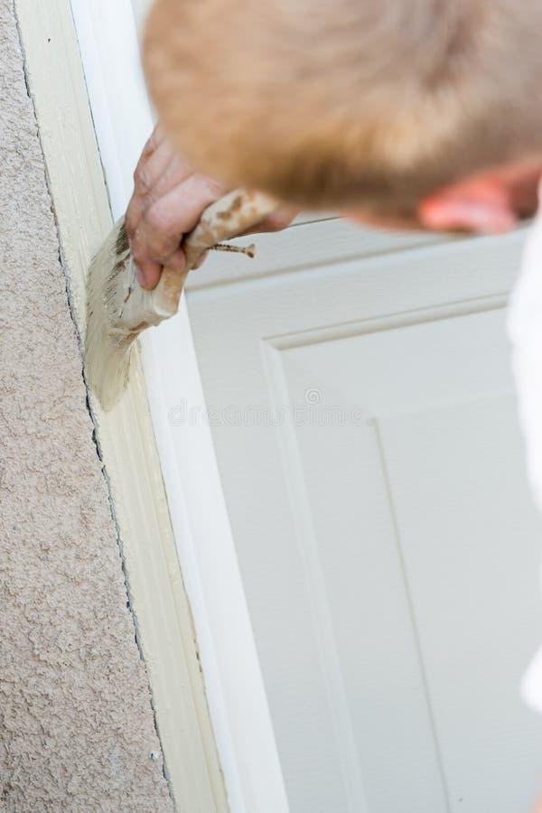 Pro-målareCutting In With borste som målar garagedörren arkivbilder