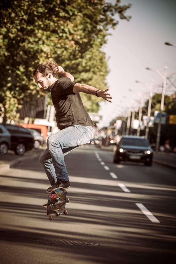 Pro patineur faisant des tours et des sauts sur la rue Tour gratuit image libre de droits