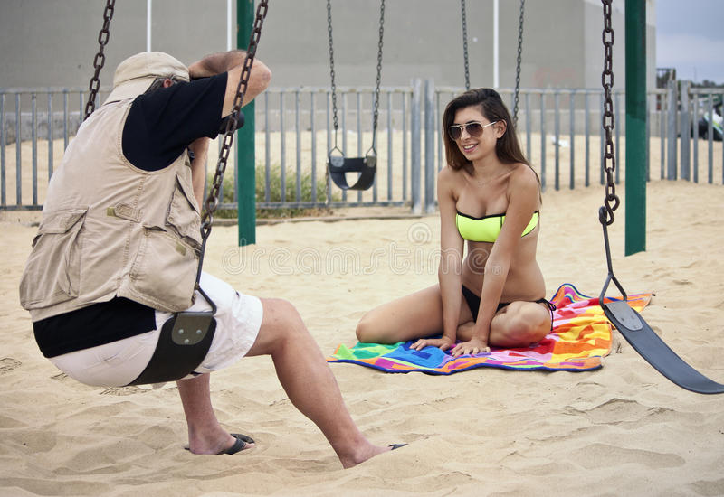 Pro Photographer Working With Models On The Beach. Professional photographer photographs a young attractive female bikini clad model on the beach in Venice Beach