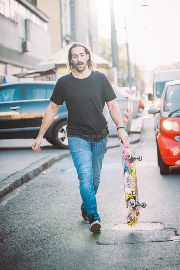 Pro promenade de cavalier de planche à roulettes en bas de la rue tenant le skatebord photo libre de droits