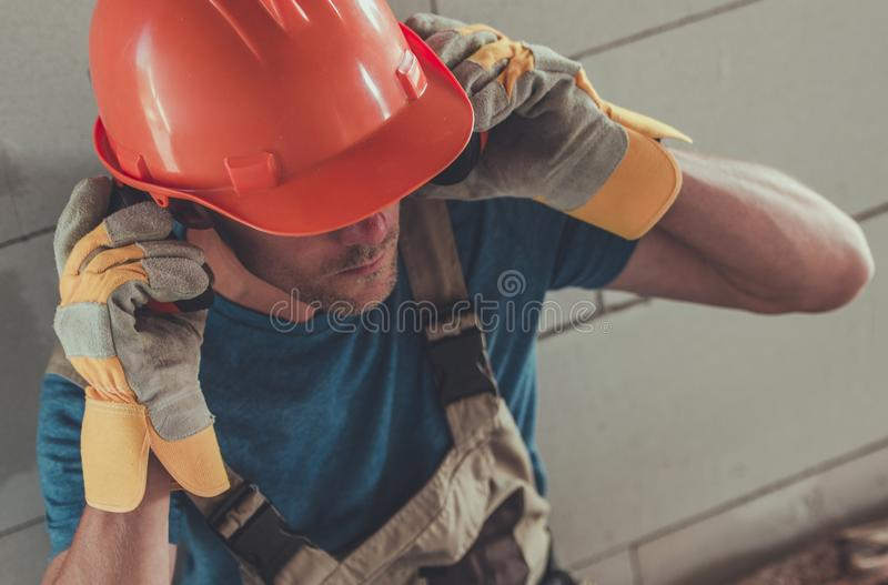 Pro Protection Equipment. Professional Construction Protection Equipment. Caucasian Contractor Wearing Noise Reduction Headphones, Hard Hat and Protection Gloves stock image