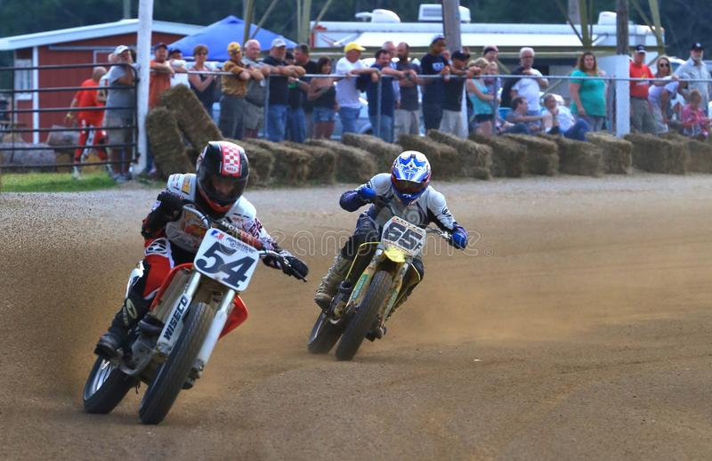 Pro racing action. Vintage motorcycles compete at a dirt race track with the spectators in the distance at the classic motorcycle racing event on the dirt oval stock photography
