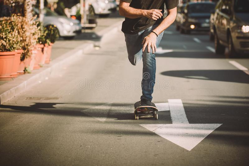Pro skateboard rider in front of car on city street. Pro skate rider ride skateboard in front of the car on the city road street through traffic jams stock photo