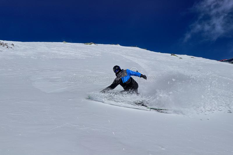 Pro skier makes curving on  powder snow down the slope against the backdrop of the mountains in Low tatras, Slovakia. Concept of royalty free stock image