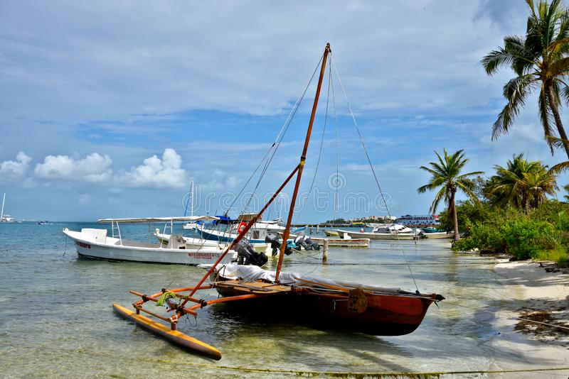 Proa dinghy. Proa dinghy on the beach of isla Mujeres. Mexico. A proa, also seen as prau, perahu, and prahu, or prow. It is a vessel consisting of two usually royalty free stock image
