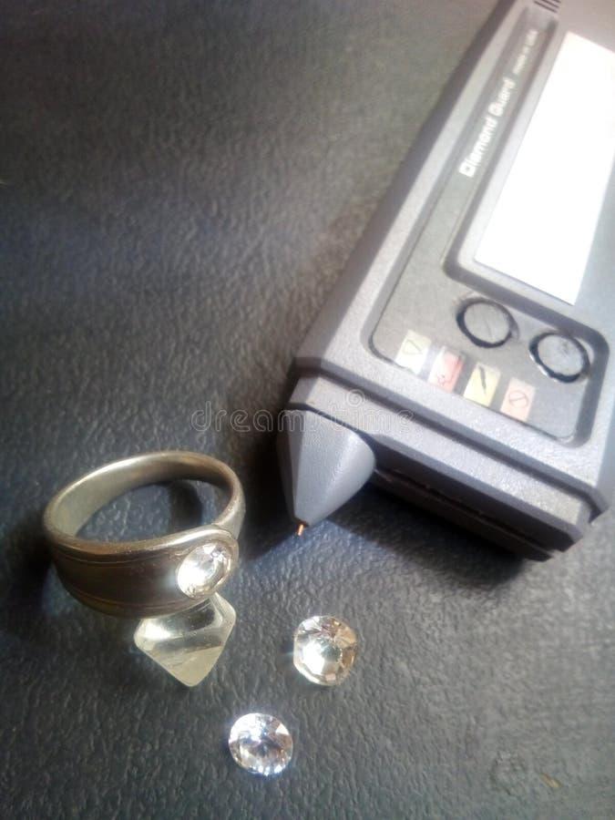 Probador del diamante con el anillo y las piedras fotos de archivo