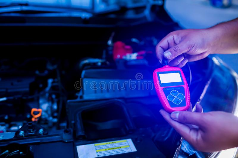 Probador masculino de la batería de la tenencia del mecánico después de cambiar la batería de coche fotos de archivo